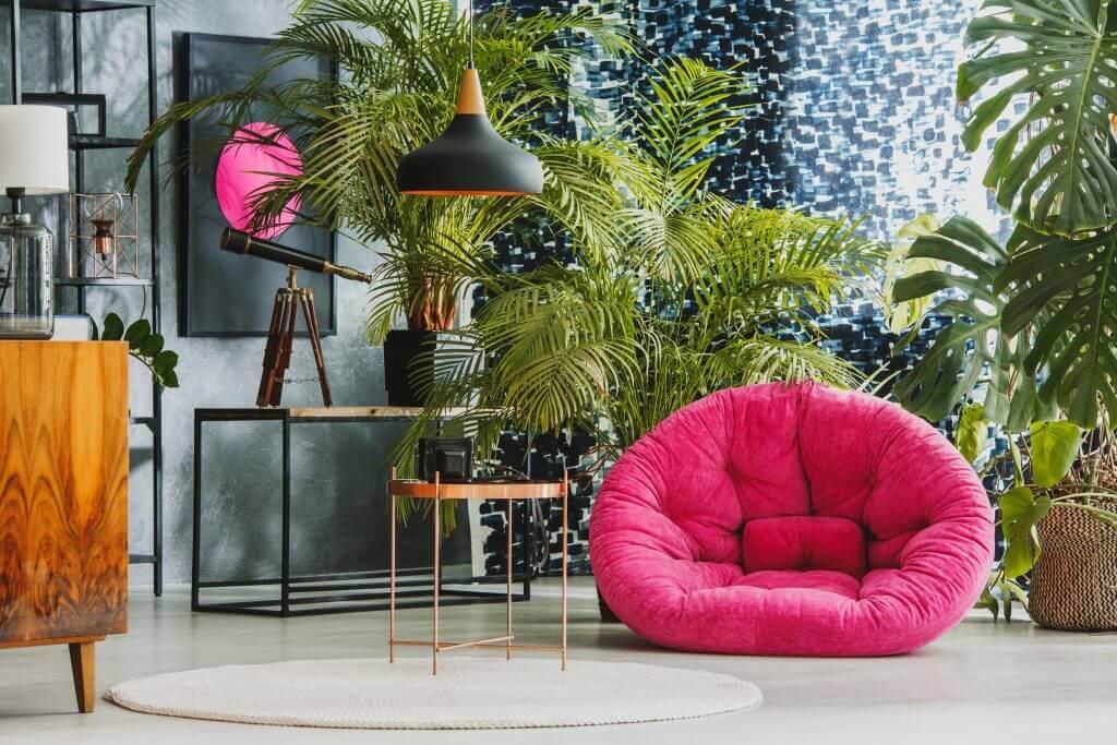 Living spațios cu fotoliu de pluș roz, telescop și plante exotice